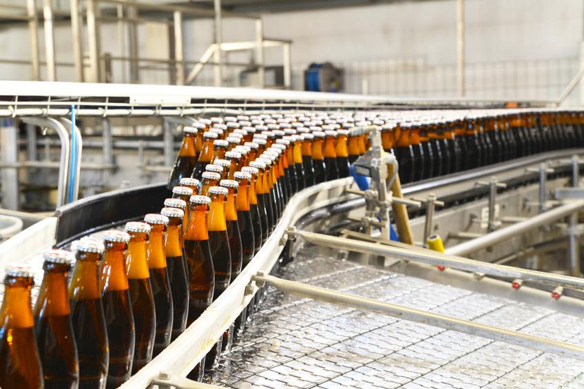 Fliessband mit Bierflaschen in einer Brauerei – automatisierte Industrieanlage // bottles in a brewery